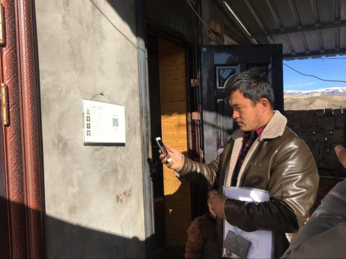 A government official scans the QR code on the wall of a home in Xinjiang, which gives him instant access to the residents' personal information.