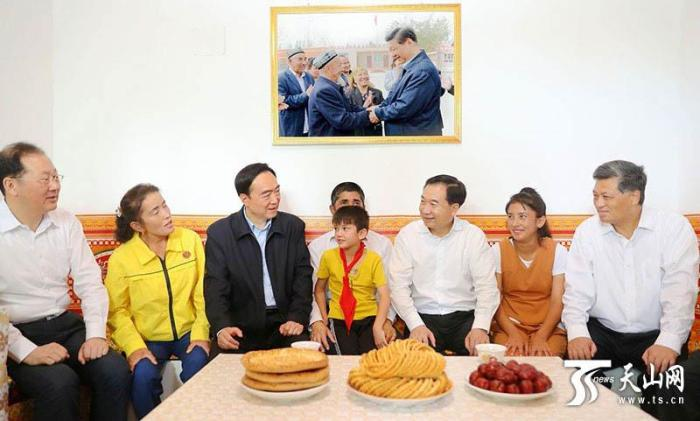 Xinjiang Party Secretary Chen Quanguo (third from left) in a state press photo visiting a Turkic Muslim family in Xinjiang.