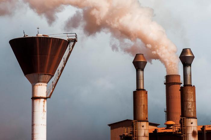 A chimney emits smoke at a bauxite treatment plant operated by Compagnie des Bauxites de Guinee (CBG) in Kamsar, Guinea, on September 7, 2015. Local leaders have long expressed concerns about the impacts of the emissions on local air quality.