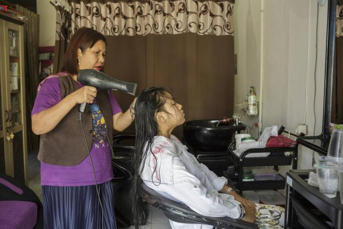 A woman with a psychosocial disability is working in her hair salon.