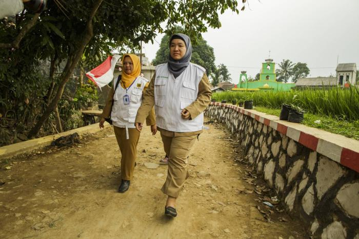Two community health workers walking in a village in Indonesia.