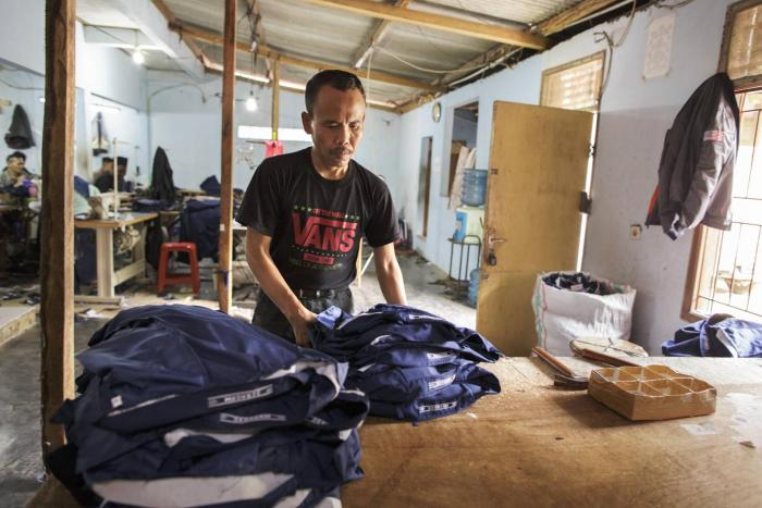 Man working in a clothing factory in Indonesia, stitching buttons