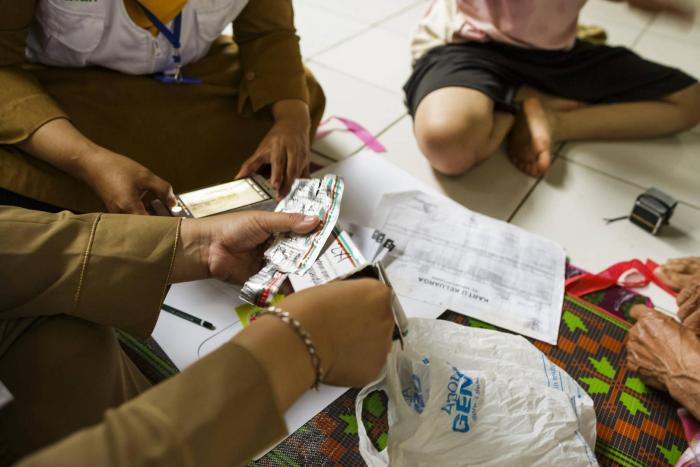 Community health workers give medication to local residents in their home in Indonesia