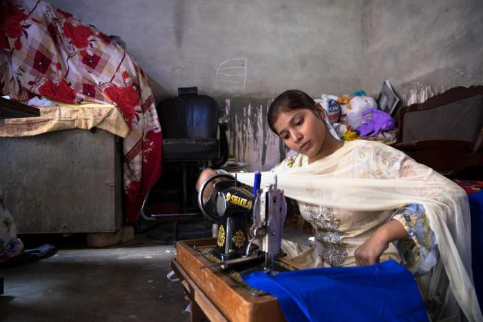 Bushra, a 10th grader, sews to help earn money for her school expenses. her mother is a seamstress. education costs often increase as children advance in grades, and while many poor families go to great lengths to access education for their children