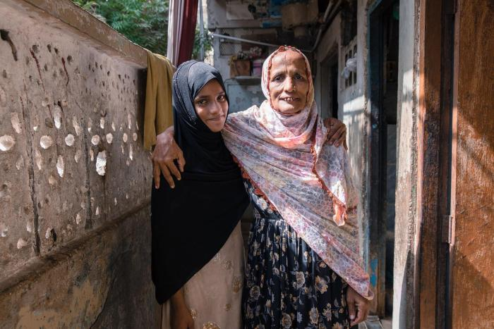 Saba, age 11, who does not attend school, with her mother.