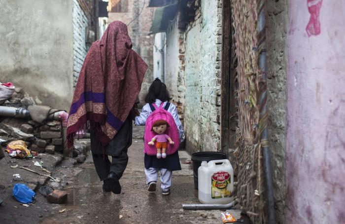 A mother takes her daughter to school in Islamabad. government schools generally offer free tuition, but parents and students are still obliged to pay for uniforms, school supplies, and exams fees.