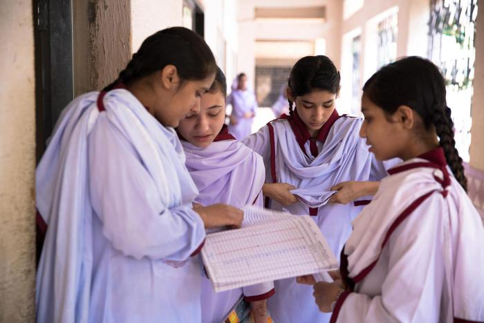 Students check the attendance register at Behar colony government Secondary School for girls in the lyari neighborhood of Karachi, Pakistan.