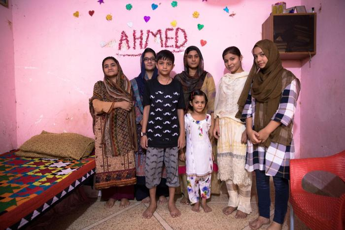 Bushra, second from the right, a 10th grader at Behar colony government Secondary School for girls, at home with her family. Bushra's mother, far left, never studied; she married at age 14.