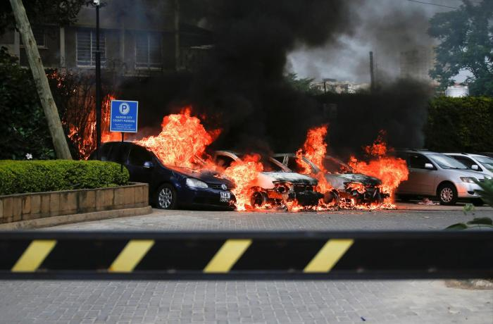 Burning cars are seen at the scene where explosions and gunshots were heard at the Dusit hotel compound, in Nairobi, Kenya January 15, 2019.