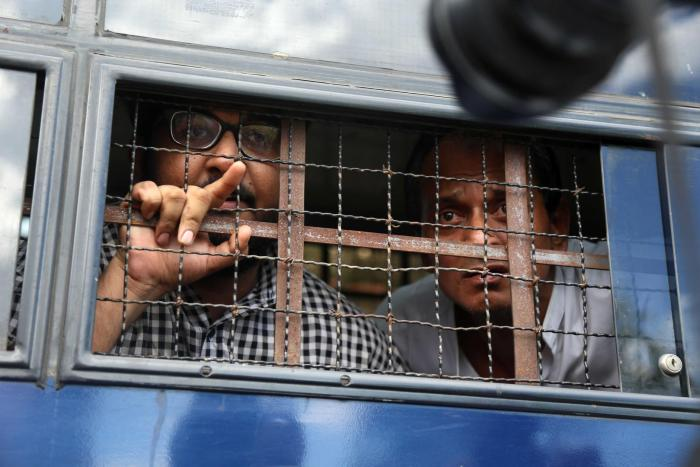Myanmar journalist Aung Naing Soe (left) and driver Hla Tin look out from a prison transport vehicle after being sentenced by a court in Naypyidaw, November 10, 2017.
