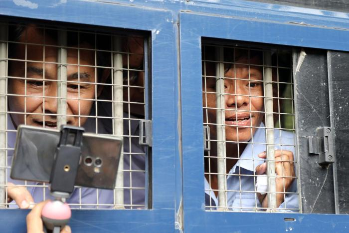 Journalists Aye Nai (left) and Lawi Weng speak to reporters from inside a prison transport vehicle outside the courthouse in Hsipaw, Shan State, July 28, 2017.