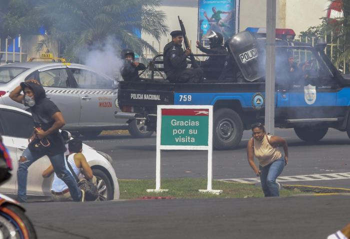An officer of the National Police shoots at a group of people outside the shopping mall Metrocentro in Managua, Nicaragua, May 28, 2018.