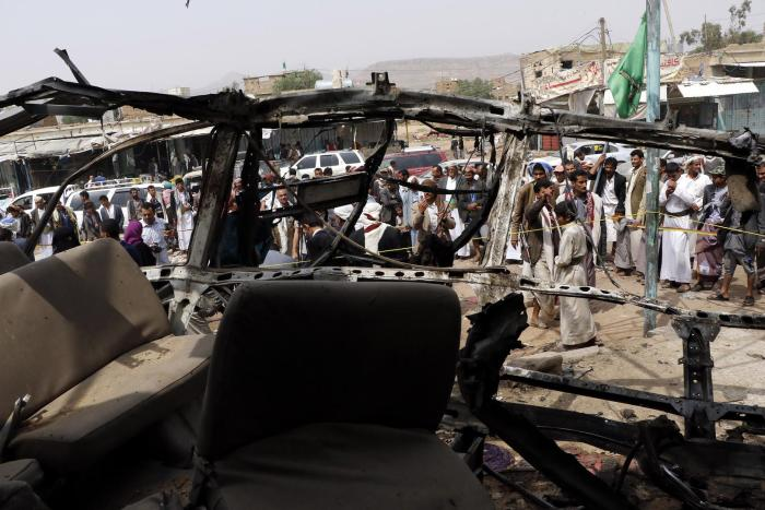 People are seen near a bus destroyed by an airstrike that killed dozens of children, in a photograph taken on August 12, 2018 in Saada, Yemen.
