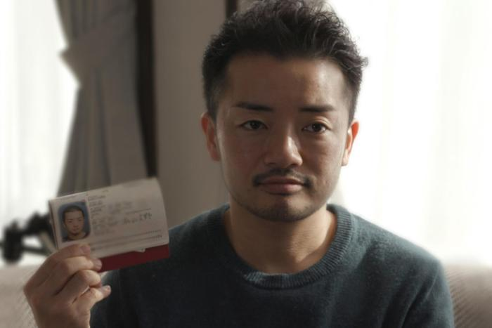 "Fumino Sugiyama, a transgender man, holds his Japanese ID card, which reads ""female,"" at his home in Tokyo."