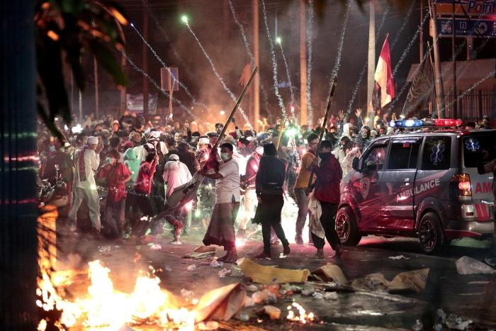 Fire crackers explode near supporters of presidential candidate Prabowo Subianto during clashes with the police in Jakarta, Indonesia, Wednesday, May 22, 2019.
