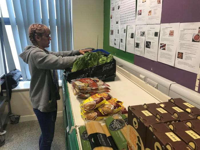 """Sarah Nor,"" a volunteer and pantry user at the Goodwin Community Pantry in Hull, puts fresh produce on the shelves, June 2018. The pantry receives redistributed food from a local scheme and makes it available to community members at low cost."