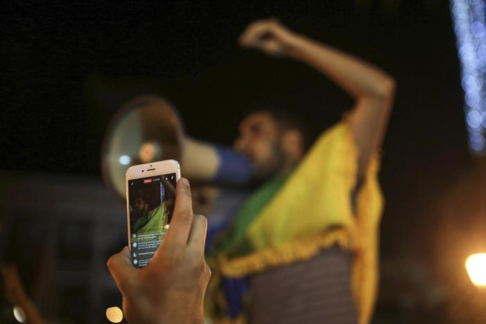 A citizen documenting a street protest with a smartphone in Morocco.