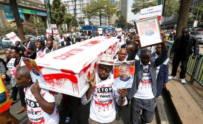 Protesters carry photos of taxi driver Joseph Muiruri, who was killed extrajudicially alongside human rights lawyer Willie Kimani and his client, in Nairobi, Kenya, on July 4, 2016.