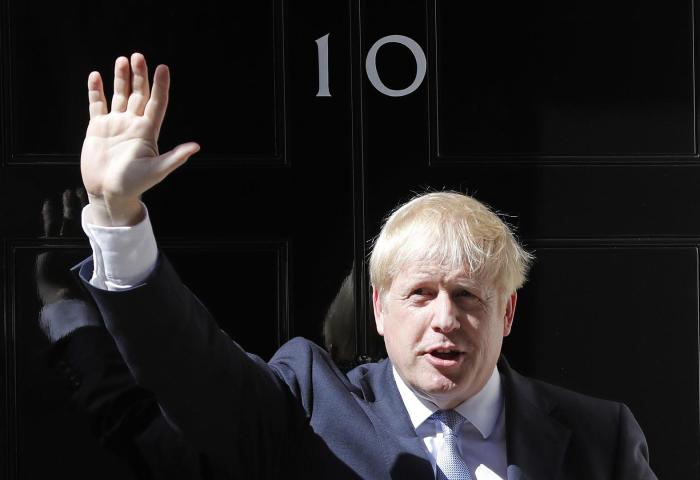 Britain's new Prime Minister Boris Johnson waves from the steps outside 10 Downing Street, London, on Wednesday, July 24, 2019.