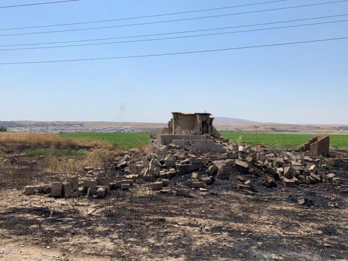 A destroyed home near Ashqala al-Sagheer village in Hamdaniya, July 2019. Hasansham camp is in the background.  © 2019 Belkis Wille/Human Rights Watch