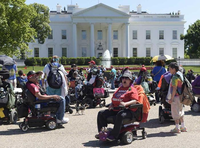 Protesters supporting people with disabilities gather outside the White House in Washington.