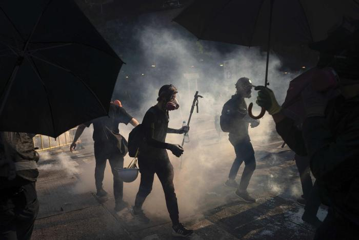 Protestors stand surrounded by smoke from tear gas shells in Hong Kong, October 1, 2019.