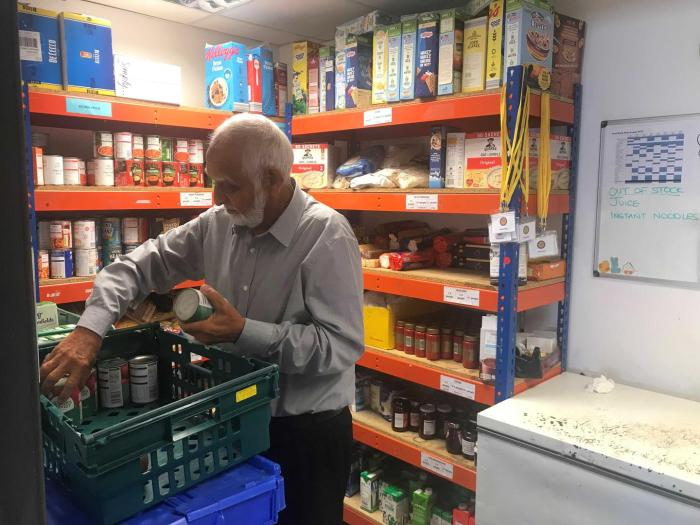 Abdalkarim Sama, a volunteer at Sufra Food Bank, sorts through tinned food in the storage section on site at Sufra Food Bank, in Brent, Northwest London. October 9, 2019