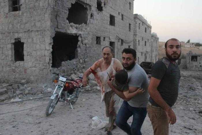 Residents rescue injured child after strike on the displacement center in Hass on August 16, 2019.