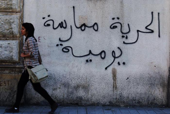 "A Tunisian woman walks past a graffiti that reads ""Freedom is a daily practice"" in Tunis April 26, 2011."