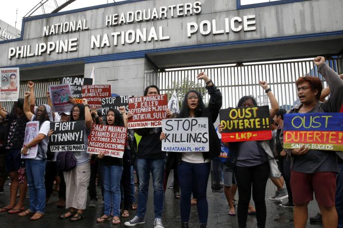 Veiled protesters, mostly relatives of victims of alleged extra-judicial killings, display placards during a protest outside the Philippine military and police camps