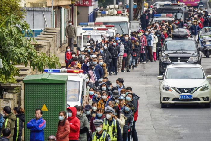 People line up to buy face masks from a medical supply company in Nanning, southern China's Guangxi Zhuang Autonomous Region.