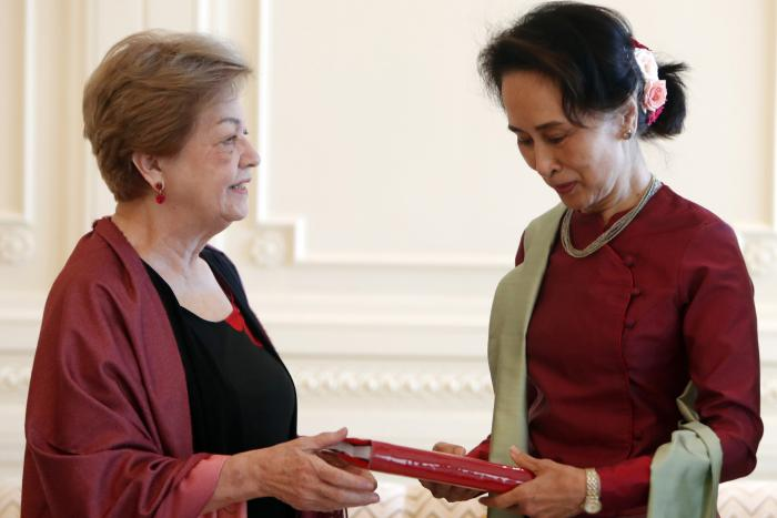 Myanmar's leader Aung San Suu Kyi, right, receives a final report from Philippine diplomat Rosario Manalo, a member of the Independent Commission of Enquiry for Rakhine State, at the Presidential Palace in Naypyitaw, Myanmar, Monday, Jan. 20, 2020.