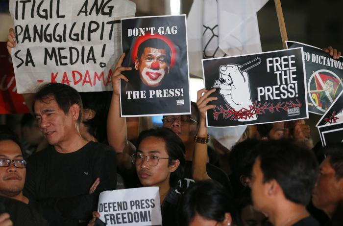Journalists and supporters, wearing black, display their messages during a protest against the recent Securities and Exchange Commission's revocation of the registration of Rappler, an online news outfit, Friday, Jan. 19, 2018, northeast of Manila, Philip