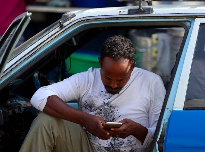 Mimiyo Fikadu, 38, taxi driver, browses through the internet using his Ethio-telecom service as he waits for his customers in Addis Ababa, Ethiopia, November 12, 2019. REUTERS/Tiksa Negeri