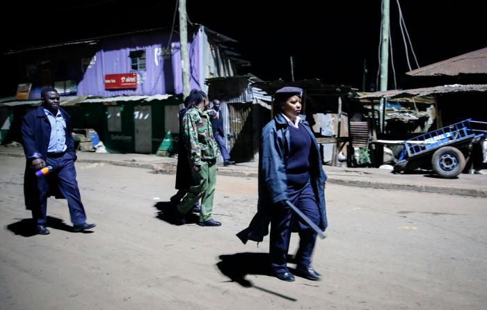 Kenyan police carrying batons and teargas patrol looking for people out after curfew in the Kibera slum, or informal settlement, of Nairobi, Kenya, March 29, 2020.