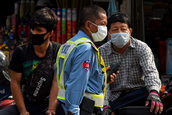 A policeman (center) and others wear face masks as a preventive measure against COVID-19, at a market in Phnom Penh on March 17, 2020.