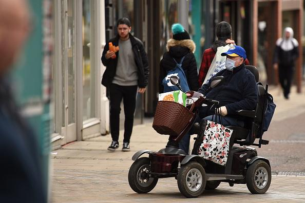 A man wears a protective face mask as he drives a mobility scooter in central Leeds on the morning of March 21, 2020.