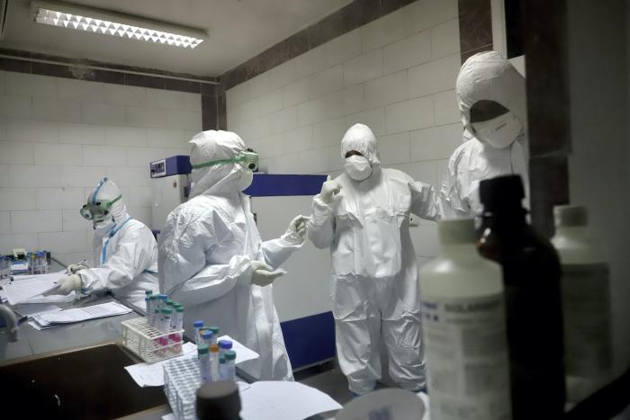 Paramedics work in a laboratory that tests samples taken from patients suspected of being infected with the new coronavirus, in the southwestern city of Ahvaz, Iran, March, 10, 2020.