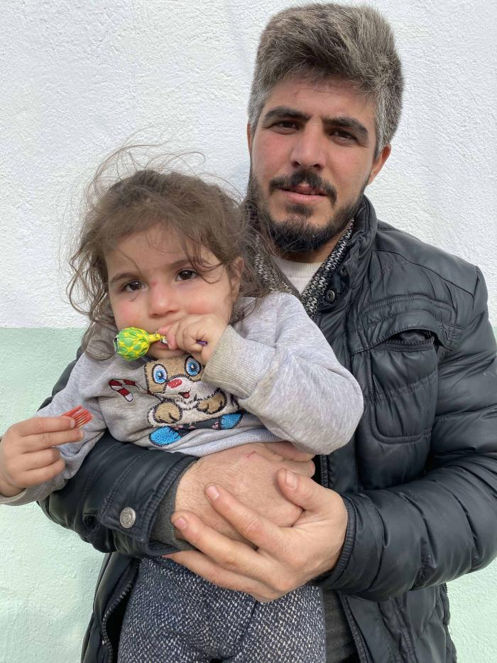 A Syrian man holds his 2-year-old daughter in the Turkish border village of Alibey on March 9, 2020, a day after he says Greek security forces detained and beat them both when he tried to stop them from sexually assaulting and stripping his wife.