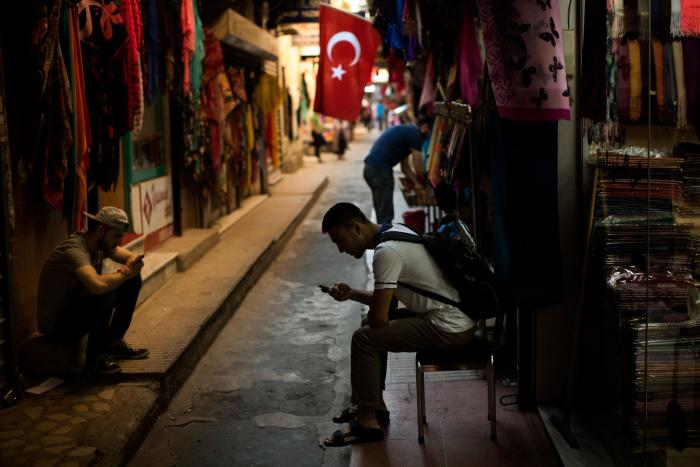 People check their phones at a market in central Istanbul, Turkey, July 18, 2019.