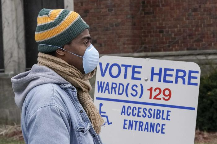 A voter wears a mask while waiting to cast ballot.