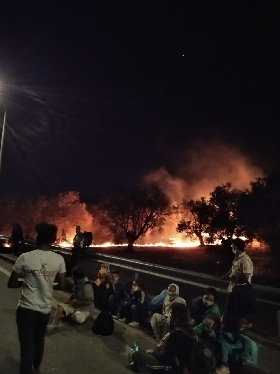 People sit on a roadside while a fire burns behind them