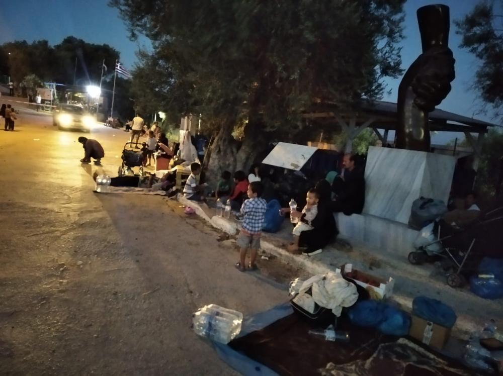 A family sits on a roadside at night with their possessions