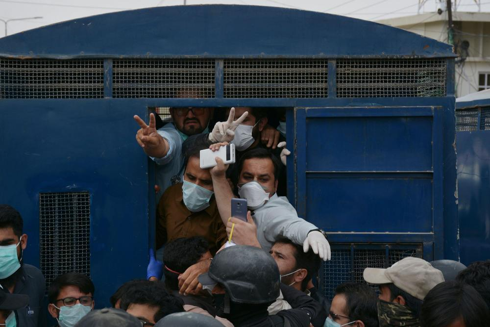 Men in masks being forced into a police van