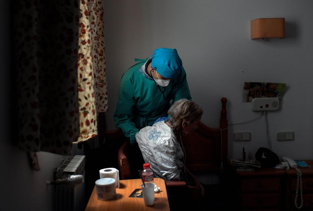 A doctor in a mask and scrubs checks on an elderly woman using a stethoscope