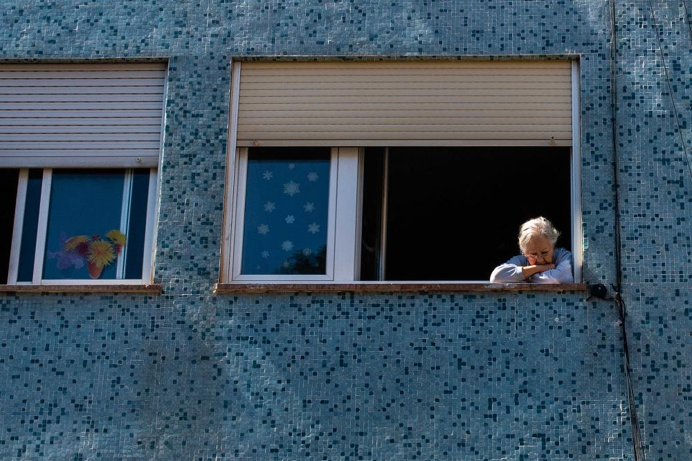 An elderly woman stares out of her apartment window