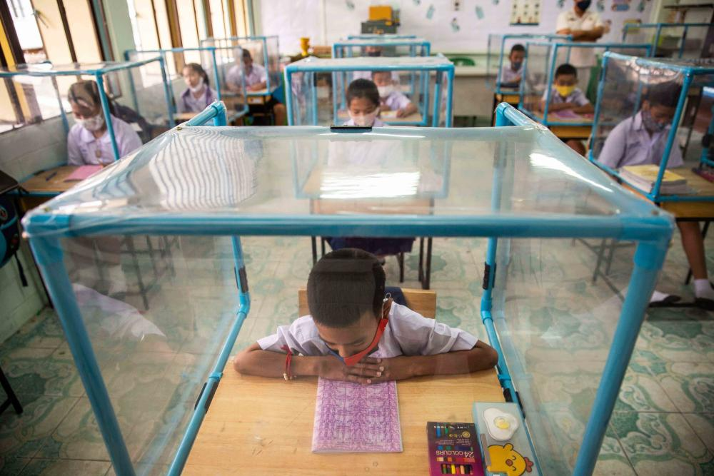 Children sit at desks enclosed with plastic screens in a classroom
