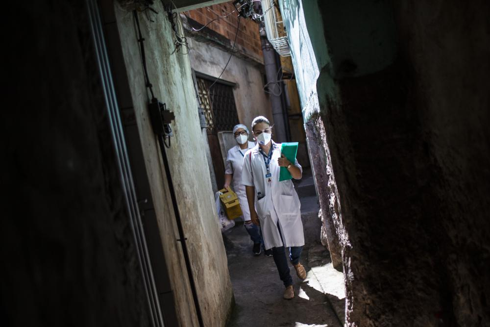 Two healthcare workers in masks walk through an alleyway
