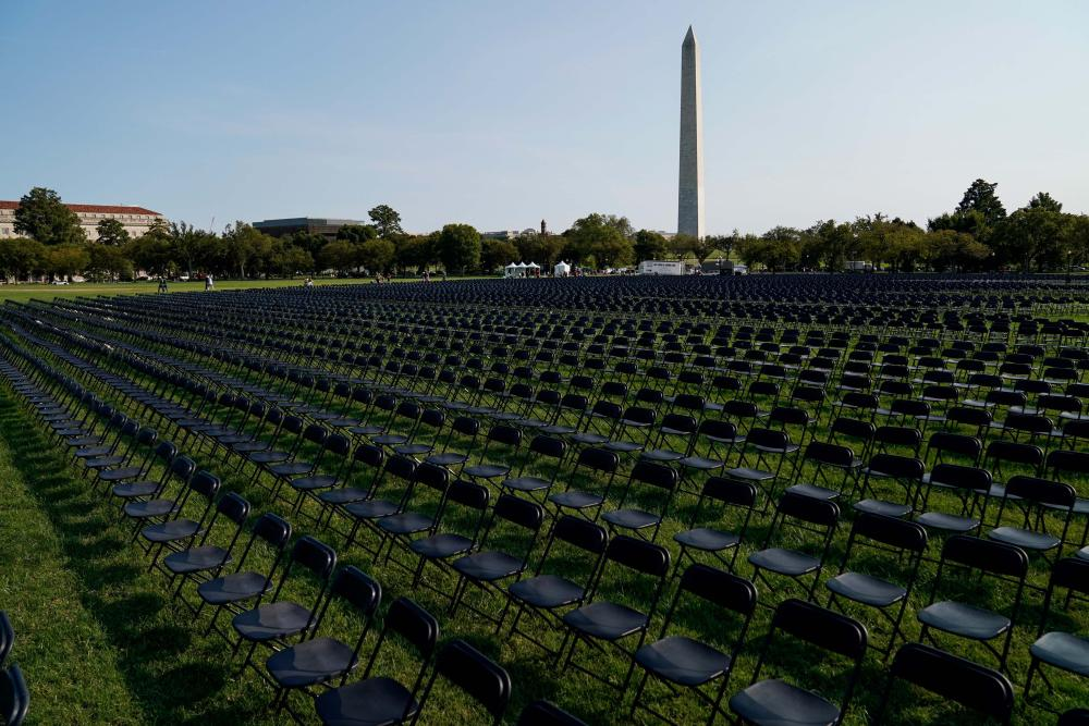 Rows of empty black chairs laid out in front of the Washington Monument