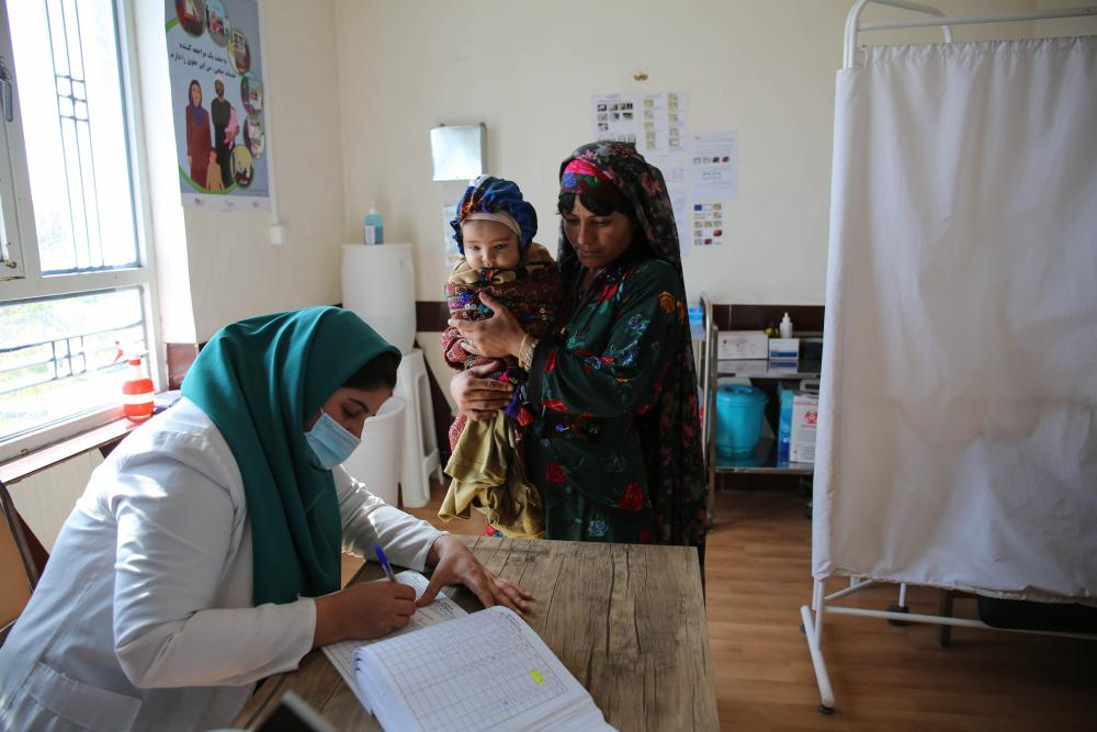 A healthcare worker fills out a form while a woman and her baby look on